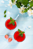 Strawberry smoothie and flower petals on blue background Royalty Free Stock Photography
