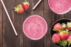 Strawberry smoothie and fresh strawberries in glass on wooden ba stock images