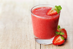 Strawberry smoothie in a glass decorated with mint leaves on rustic background, fresh fruit juice, detox food. Strawberry smoothie in a glass decorated with mint stock images