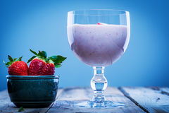 Strawberry smoothie in a glass with fresh strawberries in a bowl aside Royalty Free Stock Photos