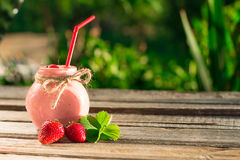 Strawberry smoothie in glass jar, over wood table. Royalty Free Stock Image