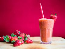 Strawberry smoothie in glass with straw. And pile of strawberries with a pink background Stock Photos
