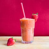 Strawberry smoothie in glass with straw. And strawberry with a pink background Royalty Free Stock Photography