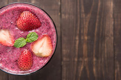 Strawberry smoothie in glass on wooden background, with a lot of Stock Image