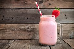 Strawberry smoothie in a mason a jar over rustic wood Royalty Free Stock Image