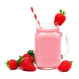 Strawberry smoothie in a mason jar with straw and berries over white. Pink strawberry smoothie in a mason jar glass with straw and scattered berries isolated on Stock Image