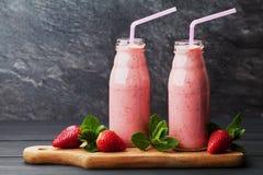 Strawberry smoothie or milkshake in jar on black rustic background, healthy food for breakfast Stock Photo