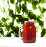 Strawberry smoothie or milkshake in a jar on green leaves background. Stock Photos