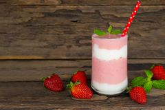 Strawberry smoothies colorful fruit juice beverage healthy the taste yummy In glass drink episode morning on wooden background. Strawberry smoothie or milkshake royalty free stock images