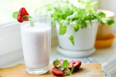 Strawberry smoothie or milkshake in jar on white rustic background, healthy food for breakfast. And snack stock image