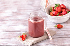 Strawberry smoothie or milkshake in jar on white wooden rustic background. Healthy food for breakfast and snack Royalty Free Stock Images