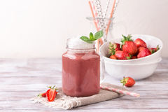 Strawberry smoothie or milkshake in jar on white wooden rustic background. Healthy food for breakfast and snack Royalty Free Stock Photo