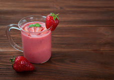 Strawberry smoothie on a wooden background. Glass of strawberry smoothie on a wooden background Stock Photos
