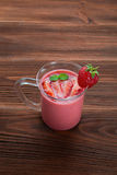 Strawberry smoothie on a wooden background. Glass of strawberry smoothie on a wooden background Stock Images