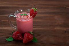 Strawberry smoothie on a wooden background. Glass of strawberry smoothie on a wooden background Stock Photo