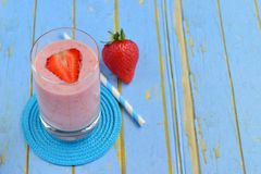 Strawberry smoothie. Strawberry yogurt smoothie in glass on blue background Royalty Free Stock Images