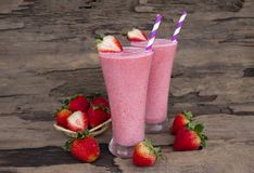 Strawberry smoothies colorful fruit juice beverage healthy the taste yummy In glass drink episode morning on wooden background. Strawberry smoothie or milkshake royalty free stock photos