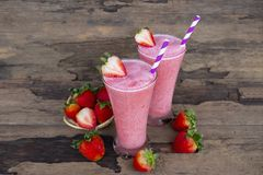 Strawberry smoothies colorful fruit juice beverage healthy the taste yummy In glass drink episode morning on wooden background. Strawberry smoothie or milkshake stock photo
