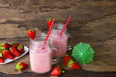 Strawberry smoothies colorful fruit juice beverage healthy the taste yummy In glass drink episode morning on wooden background. Strawberry smoothie or milkshake stock photos