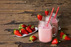 Strawberry smoothies colorful fruit juice beverage healthy the taste yummy In glass drink episode morning on wooden background. Strawberry smoothie or milkshake stock photography