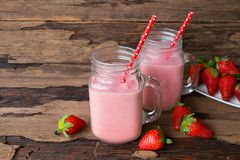 Strawberry smoothies colorful fruit juice beverage healthy the taste yummy In glass drink episode morning on wooden background. Strawberry smoothie or milkshake stock images