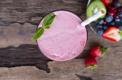 Strawberry smoothies colorful fruit juice beverage healthy  on wood background from the top view. Strawberry smoothies red colorful fruit juice milkshake blend royalty free stock images