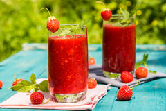 Strawberry smoothies on an old blue wooden surface Royalty Free Stock Photo