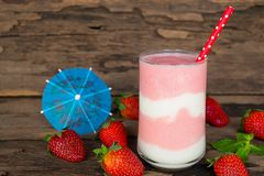 Strawberry smoothies red colorful fruit juice milkshake blend beverage healthy high protein the taste yummy In glass drink episode. Morning on wood background royalty free stock photo