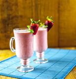 Strawberry smoothies. Strawberry smoothie with strawberry and mint with another smoothie in the background Royalty Free Stock Photos