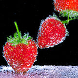 Strawberry in soda water. Strawberry with bubbles in soda water on black background Royalty Free Stock Images