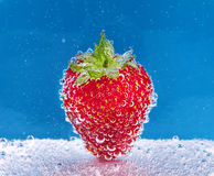 Strawberry in soda water. Strawberry with bubbles in soda water on blue background Stock Photos