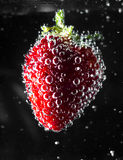 Strawberry in soda. Water bubbles macro micro berry seeds red green gray black background food kitchen pretty raspberry weightless Stock Images
