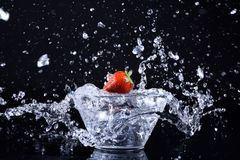 Strawberry and diamonds on wet black floor royalty free stock images