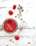Strawberry sorbet or ice-cream with fresh berries. Mint and metal scooper on over white rustic wooden backdrop, top view, copy space royalty free stock photos