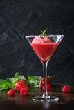 Strawberry sorbet with mint. Sugared cocktail glass of strawberry dessert with sorbet, served on dark background with Strawberries, raspberries and mint behind royalty free stock photos