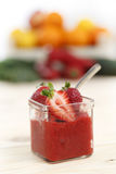 Strawberry sorbet in square glass with pieces of strawberries on light wood table Stock Photo