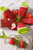 Strawberry sorbet with yogurt and mint on a stick closeup. verti. Strawberry sorbet with yogurt and mint on a stick closeup on a plate. vertical Royalty Free Stock Image