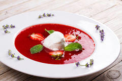 Strawberry soup with ice cream and mint. In white plate, garnished with lavender Stock Photo