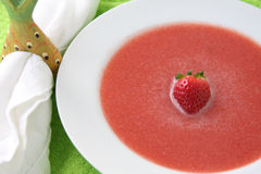 Strawberry Soup with Single Strawberry. Strawberry soup garnished with a single strawberry in a white bowl with a white napkin and napkin ring on the side Royalty Free Stock Photos