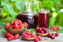 Strawberry, sour cherry and raspberry juice. In pitcher and glass Stock Photos