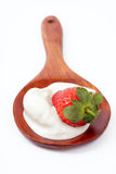 Strawberry in sour cream on a wooden spoon royalty free stock photo