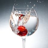 Strawberry splash. A red strawberry splashing in a glass with water Stock Photography