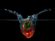 Strawberry splash. Strawberry drop on water with splash isolated in black background Royalty Free Stock Photo