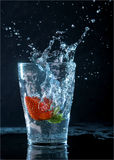 Strawberry in splash glass. With waterdrops Royalty Free Stock Images