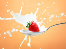 Strawberry splash in milk isolated on yellow Royalty Free Stock Images