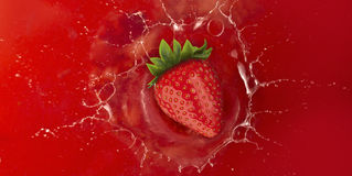 Strawberry splash into red juice Stock Photos