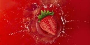 Strawberry splash into red juice Stock Photos