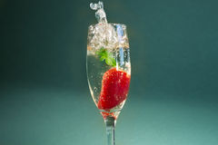 Strawberry splashing into a glass of Champagne. Royalty Free Stock Photos