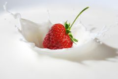 Strawberry splashing into milk Stock Photos
