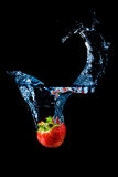 Strawberry splashing into water  on black Stock Photo